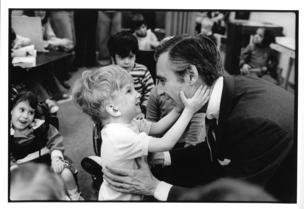 A little boy grinning and grasping Mr. Rogers's face