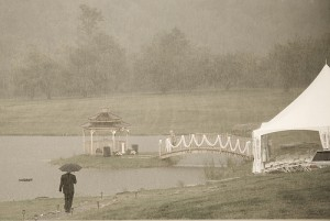 Man with an umbrella walks toward a wedding tent in pouring rain