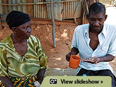 A man in Tanzania sorts his medication while his mother looks on.
