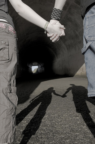 Two people holding hands at the mouth of a tunnel. Uploaded by Adam Foster on flickr