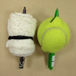Pens stuck through rolled-up washcloth and tennis ball
