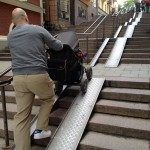 Man pushes stroller up tracks covering stairs in Stockholm