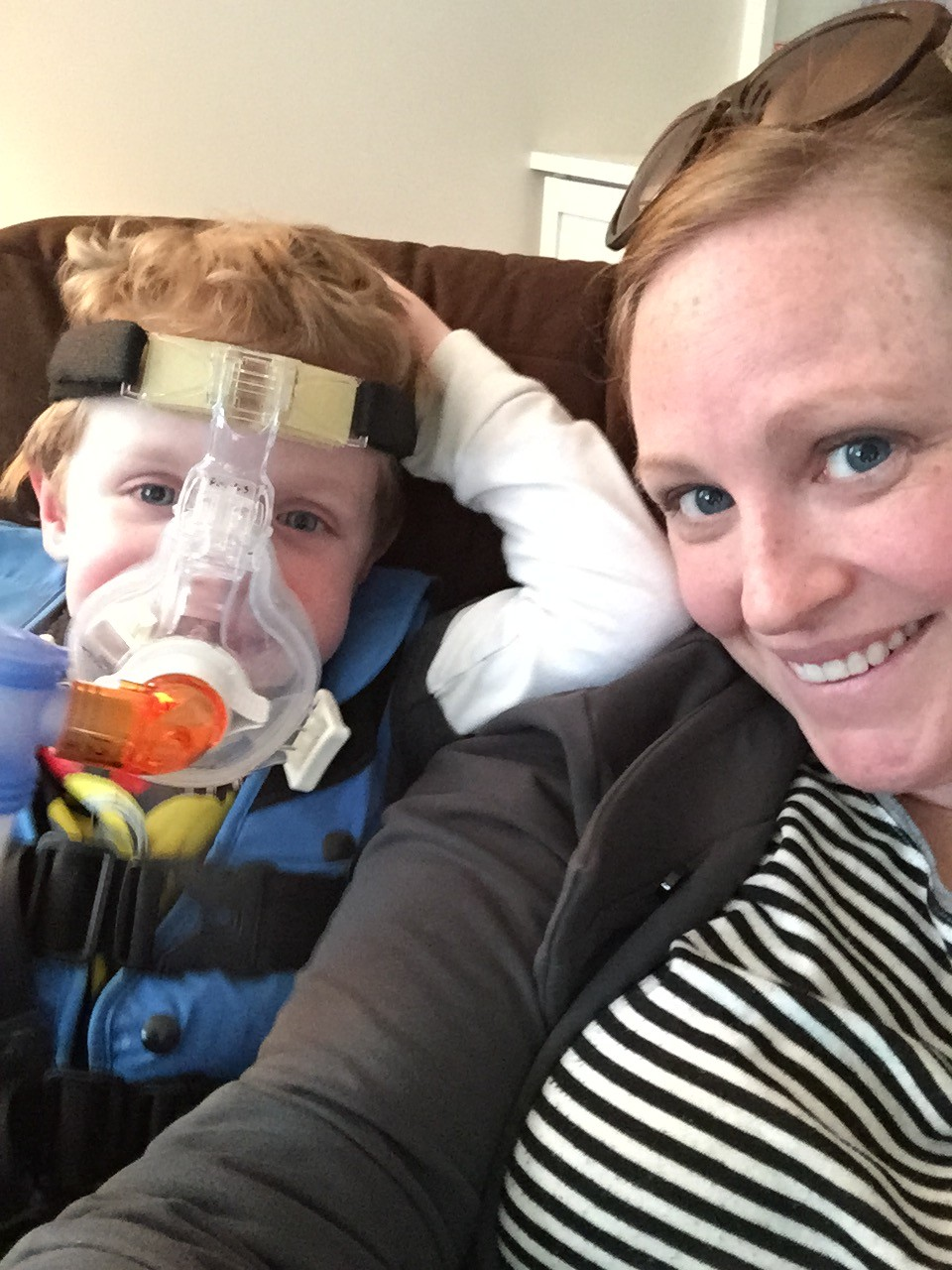 Boy wearing nebulizer mask and his mom