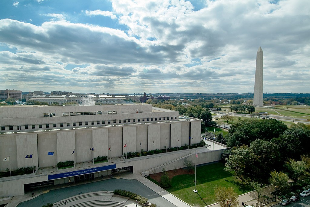 Exterior of the National Museum of American History in Washington, DC, with the Washington Monument in the background