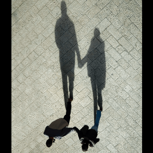 Long shadow cast by two people holding hands