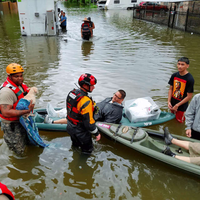 A group of men stand in knee-deep flood waters with two kayaks. One man is in a kayak.
