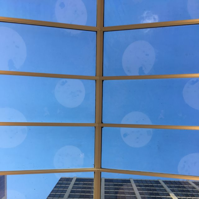 Looking up at a blue sky through a huge skylight, with white tables reflected in the glass