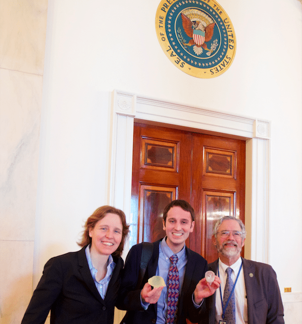 Three people standing in front of a door at the White House. One person is holding replicas of a brain tumor.