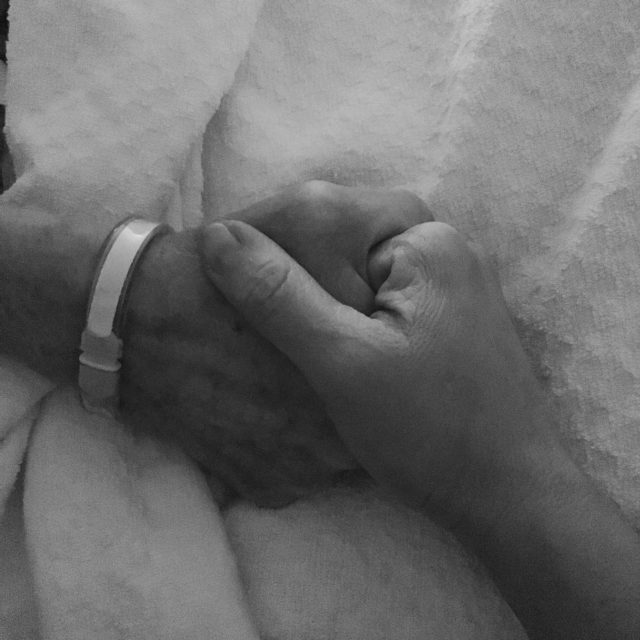 Black and white image of two hands, clasped. One person is wearing a hospital ID bracelet.