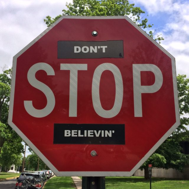 Red Stop sign with stickers, so it reads: DON'T STOP BELIEVING