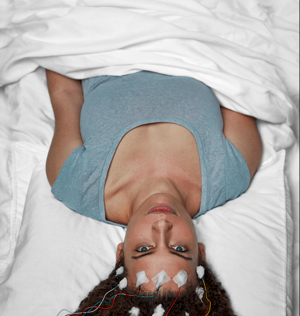 Jennifer Brea, director of the film Unrest, lies in bed with EEG leads on her head