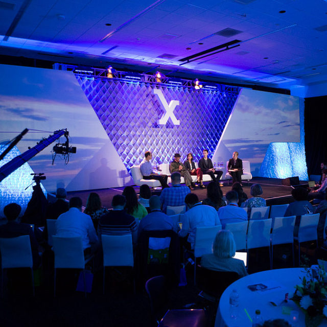 Conference stage lit up in violet with a white X hanging over the panelists
