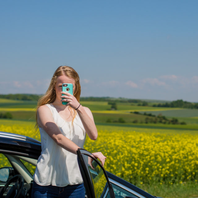 A young woman holds her phone up so it blocks her face. Background is a field of yellow flowers.