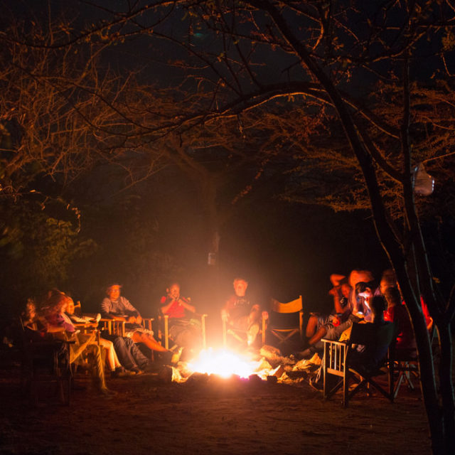 A group of adults sitting around a campfire in the woods