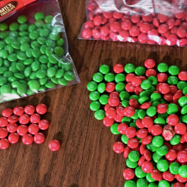 Red and green M&M candies both mixed and sorted by color