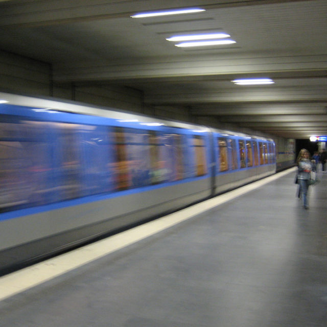 A subway train speeds away from a nearly empty platform