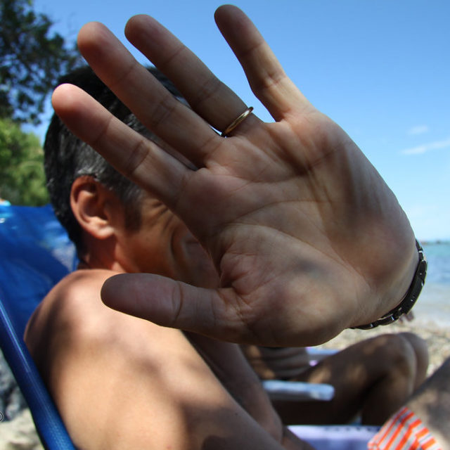 Man on a beach blocks camera with his hand