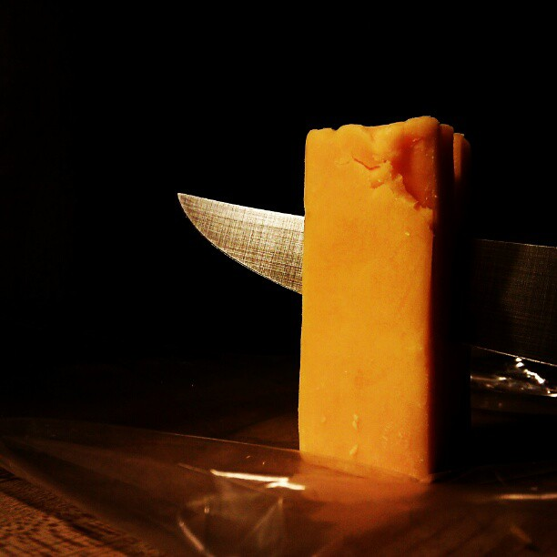 cheddar cheese being sliced by a sharp knife