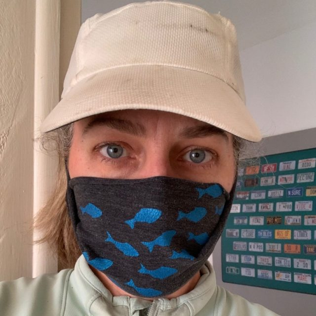 Woman wears a white baseball cap and a cloth mask over her nose and mouth
