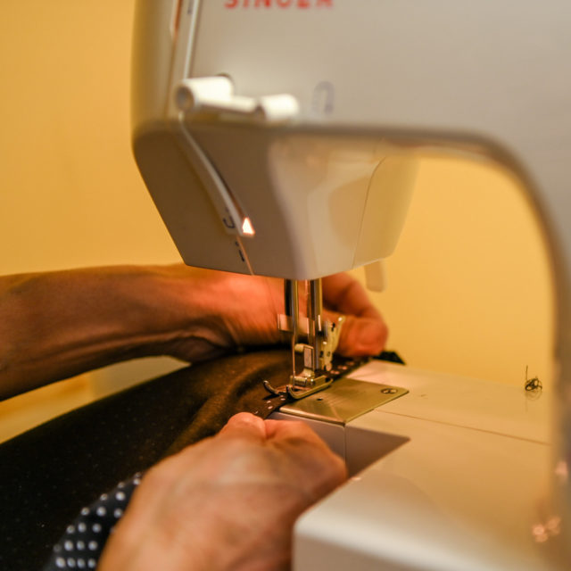 Hands feed fabric into a sewing machine