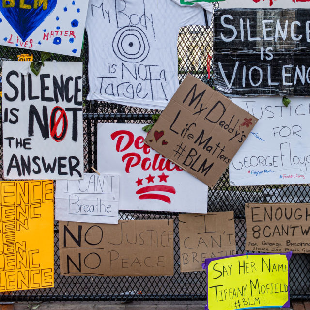 Hand painted Black Lives Matter protest signs attached to fence