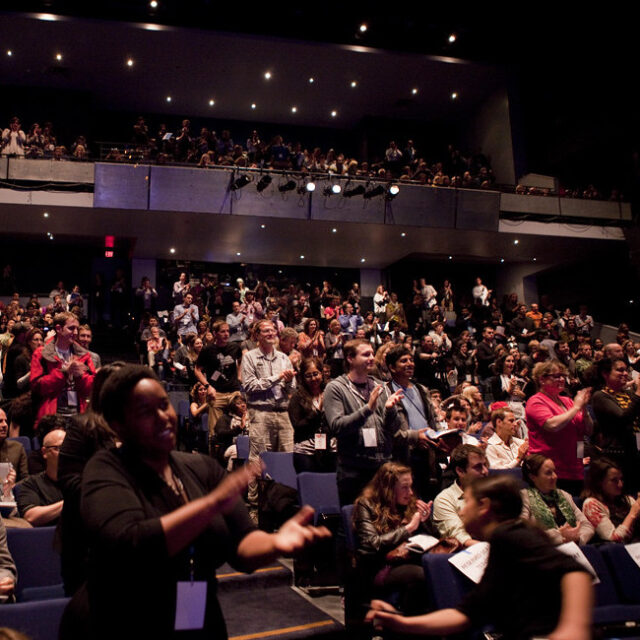 People in a crowded theater clapping, many are standing and smiling