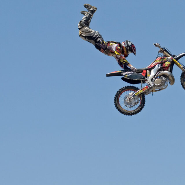 Motorbike stunt rider hanging off the seat, mid-air, against a blue sky