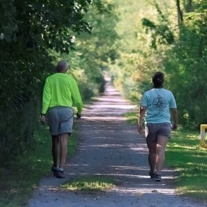 A man and woman walking on a trail